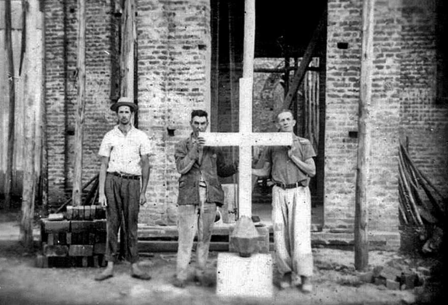 Moradores seguram a cruz da Igreja Sinodal ainda no chão: último ato