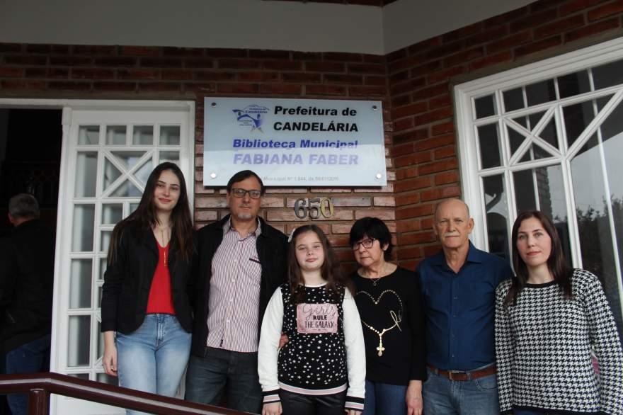 Os familiares de Fabiana junto à placa