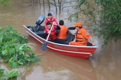 Bombeiros usaram barco para retirar moradora ilhada pela enchente