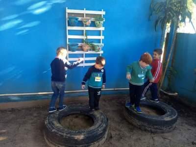 Crianças brincando com pneus, uma das ações do projeto